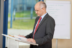 Confident Mature Businessman Reading At Podium Royalty Free Stock Image