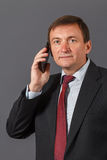 Confident mature businessman standing in front of a grey backgro Stock Image