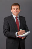 Confident mature businessman standing in front of a grey background holding a marker and writing in a notebook stock image