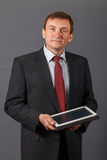Confident mature businessman standing in front of a grey background holding a notebook stock photo
