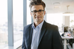 Confident mature businessman standing in office. Portrait of confident mature businessman standing in office. Caucasian male entrepreneur in suit and eyeglasses Stock Photography