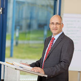 Confident Mature Businessman Standing At Podium Royalty Free Stock Images