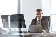 Confident mature businessman using laptop at desk in office Stock Photos