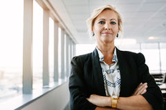 Confident mature businesswoman standing in office stock photos