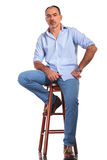 Confident mature casual man posing seated on chair. While looking at the camera in white isolated studio background Royalty Free Stock Image