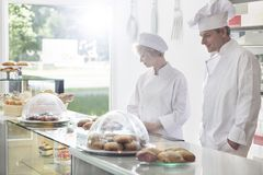 Confident mature chef coworkers standing at dessert counter in restaurant royalty free stock image