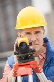 Confident Mature Construction Worker With Theodolite Royalty Free Stock Image