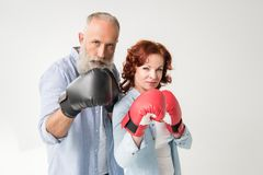 Mature couple in boxing gloves. Confident mature couple in boxing gloves, isolated on white Royalty Free Stock Image