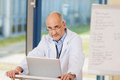 Confident Mature Doctor With Laptop At Podium Stock Photography
