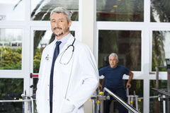 Confident Mature Doctor Smiling At Rehab Center royalty free stock photography