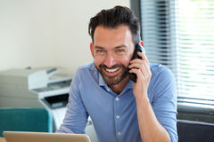 Confident mature guy talking on mobile phone and smiling Stock Photos