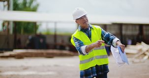 Engineer explaining while holding blueprint. Confident mature male engineer explaining while holding blueprint against timber pile at industry stock video