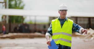 Engineer explaining while holding blueprint. Confident mature male engineer explaining while holding blueprint against timber pile at industry stock footage