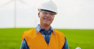 Male Engineer Working While Holding Blueprint. Confident mature male engineer holding blueprint. Industry Worker stock footage