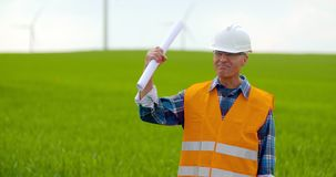 Male Engineer Working While Holding Blueprint. Confident mature male engineer holding blueprint. Industry Worker stock video footage