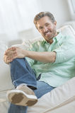 Confident Mature Man Sitting On Sofa Stock Images