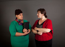 Confident Mature Plus Size Buisiness Women. Two confident plus size business women staring at each other with tension in their faces Royalty Free Stock Photos