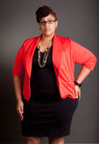 Confident Mature Plus Size Buisiness Women. Plus size black woman wearing glasses in a smart business outfit on a neutral grey background Stock Photo
