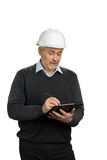 Confident mature supervisor writing on clipboard. Senior man in white helmet writing on black clipboard, white background Stock Photo