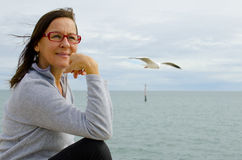 Confident Mature Woman. A confident and happy mature woman is sitting at the ocean while a seagull is flying by and watching her royalty free stock photography