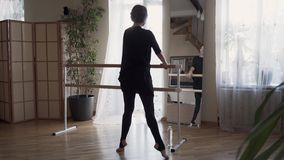 Confident mature woman dancing in front of the mirror at home. Elegant slim woman in black clothes doing exercises. Indoors. Happy life, keeping in shape stock video footage