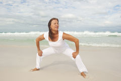 Confident mature woman exercising beach Stock Photography