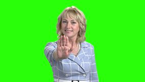 Confident mature woman making gesture stop. Elegant middle-aged business woman gesturing stop sign on chroma key background. Human body language stock video footage