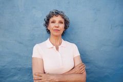 Confident mature woman standing with her arms crossed Royalty Free Stock Photos