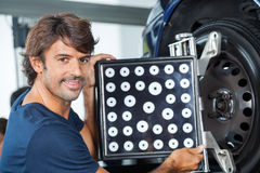 Confident Mechanic Adjusting Wheel Aligner On Car Stock Photo