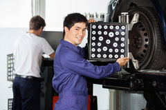 Confident Mechanic Adjusting Wheel Aligner On Car Tire Royalty Free Stock Photos