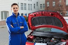 Confident mechanic with arms crossed standing by car. Portrait of confident mechanic with arms crossed standing by car on street royalty free stock image