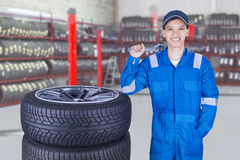 Confident mechanic carrying a wrench. Picture of a male mechanic smiling in the workshop while wearing uniform and holding a wrench near the tires Stock Image