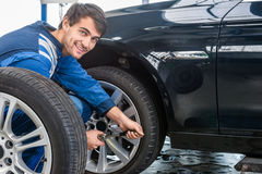 Confident Mechanic Changing Car Tire At Automobile Shop Stock Images
