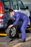 Confident Mechanic Fixing Car Tire Royalty Free Stock Photos