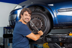 Confident Mechanic Fixing Car Tire With Rim Wrench Stock Photos
