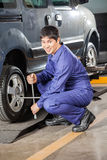 Confident Mechanic Fixing Car Tire With Rim Wrench Stock Photography