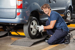 Confident Mechanic Fixing Car Tire At Workshop Royalty Free Stock Photography