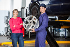 Confident Mechanic Holding Alloy With Customer Royalty Free Stock Photography