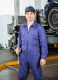 Confident Mechanic Holding Rim Wrench At Garage Stock Images