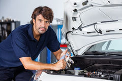 Confident Mechanic Leaning On Car With Open Hood Stock Image