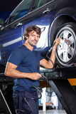 Confident Mechanic Refilling Air Into Car Tire At Garage Stock Photography