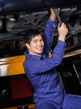 Confident Mechanic Repairing Underneath Car royalty free stock photography