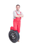 Confident mechanic resting foot on car wheel Stock Photography