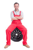Confident mechanic sitting on car wheel tire Stock Image