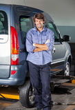 Confident Mechanic Standing Arms Crossed By Car. Portrait of confident mechanic standing arms crossed by car at garage royalty free stock images