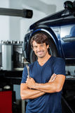 Confident Mechanic Standing Arms Crossed At Garage. Portrait of confident mechanic holding wrench while standing arms crossed at garage stock photos