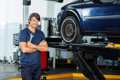 Confident Mechanic Standing Arms Crossed At Garage. Portrait of confident mechanic holding wrench while standing arms crossed at garage Royalty Free Stock Photos