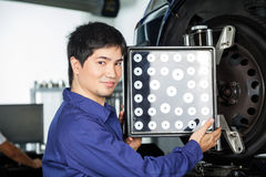 Confident Mechanic Using Wheel Aligner On Car Stock Photography