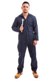 Confident mechanic with a wrench. Portrait of a young mechanic wearing overalls and holding a wrench at work on a white background royalty free stock photography