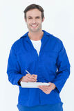 Confident of mechanic writing notes on clipboard. Portrait of confident of mechanic writing notes on clipboard over white background Royalty Free Stock Photos